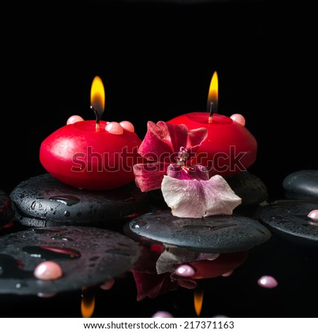 spa still life of red candles, zen stones with drops, orchid cambria flower and pearl beads in water, black background, closeup - stock photo