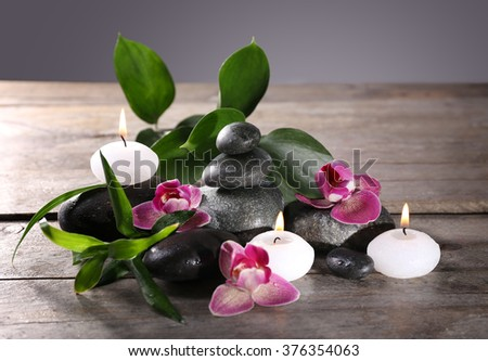 Spa still life with beautiful flower and candlelight on wooden table closeup - stock photo