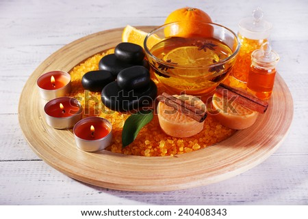 Spa still life with candle light and pebble on wooden plate, on color wooden background - stock photo