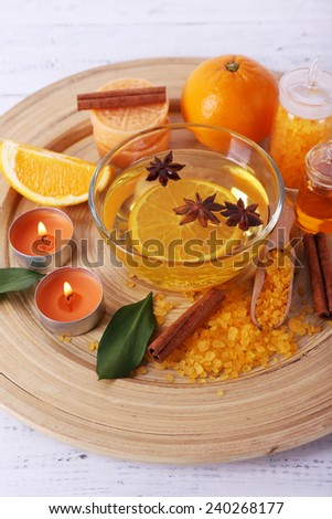 Spa still life with candle light on wooden plate, on color wooden background - stock photo