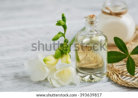 Spa still life with perfume and aromatic oil bottle surrounded by freesia flowers, on light background - stock photo