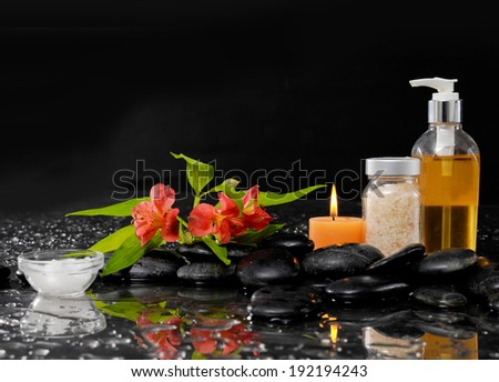 Spa Still life with red flower, massage oil, candle and zen stones - stock photo