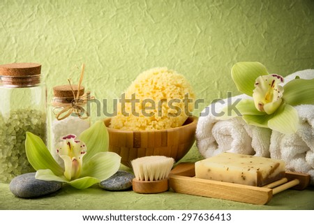 Spa still life with salt,towel,sponge,handmade soap and blooming orchid - stock photo