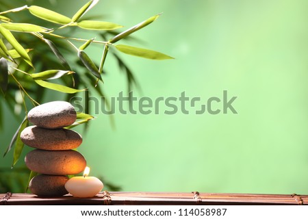 Spa still life with stacked of stone,burning candle and bamboo leaf - stock photo