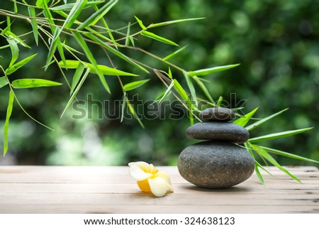 Spa still life with stacked of stone, flower candle and bamboo leaf - stock photo