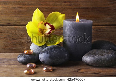 Spa still life with stones, flower and candlelight on wooden background - stock photo