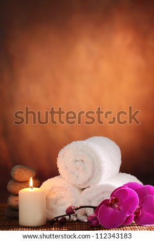 Spa still life with towel,aromatic candle and orchid flower. - stock photo