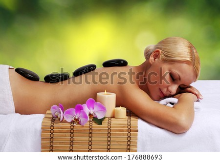 Spa Stone Massage. Beautiful Blonde Woman Getting Hot Stones Massage in Spa Salon. Beauty Treatments.  - stock photo