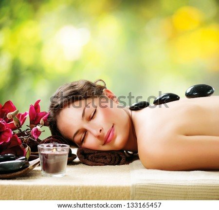 Spa Stone Massage. Beautiful Woman Getting Spa Hot Stones Massage in Spa Salon. Beauty Treatments Outdoor. Nature - stock photo