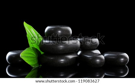Spa stones and green leaves on black background - stock photo