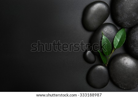 Spa stones and leaves on black background - stock photo