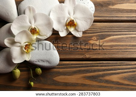 Spa stones and orchid flower on wooden background - stock photo