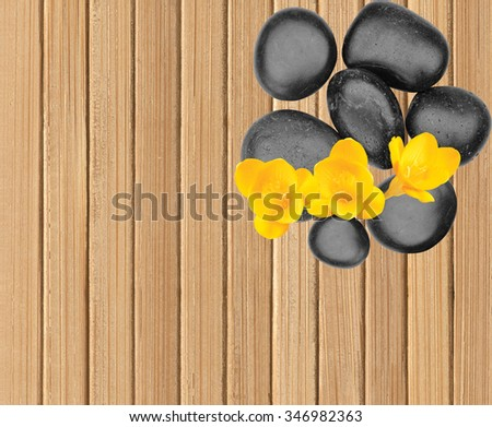 Spa stones and yellow flower on wooden table background - stock photo