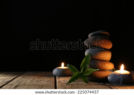 Spa stones, candles on wooden table on dark background - stock photo