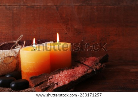 Spa stones with candles and sea salt on wooden background - stock photo