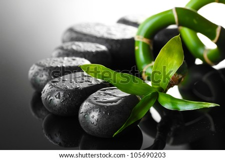 Spa stones with drops and green bamboo on grey background - stock photo