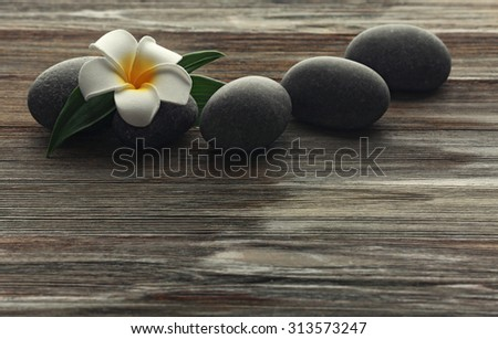 Spa stones with flower on wooden background - stock photo