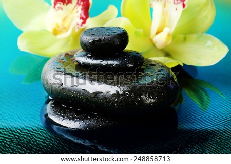 Spa stones with water drops and beautiful blooming orchid in water close-up - stock photo