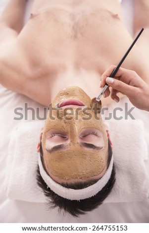 Spa therapy for young asian woman receiving facial mask at beauty salon. - stock photo