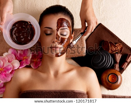 Spa therapy for young woman having cosmetic mask at beauty salon - stock photo