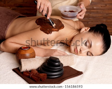 Spa therapy for young woman receiving cosmetic mask on back at beauty salon - stock photo
