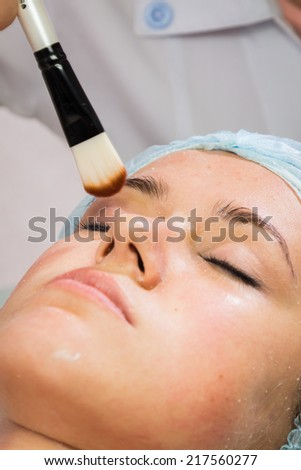 Spa therapy for young woman receiving facial mask at beauty salon - indoors.Beautiful woman with facial mask at beauty salon.Woman with clay facial mask in beauty spa - stock photo