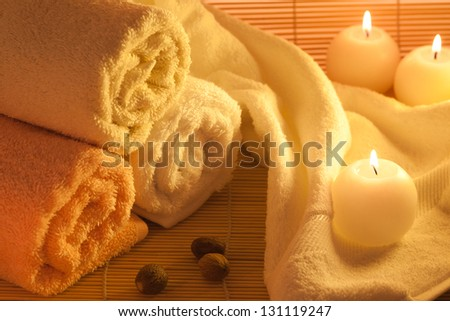 Spa towels, candle and nuts on bamboo background - stock photo