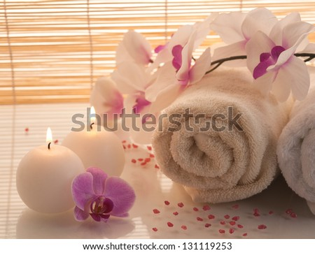 Spa towels, candle and orchid on bamboo background. - stock photo