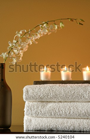 Spa towels, candles and vase with flowers - stock photo