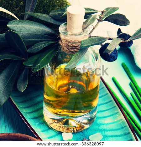 Spa treatment. Close-up of bottle with olive oil, olive tree twig and green aromatic sticks - stock photo