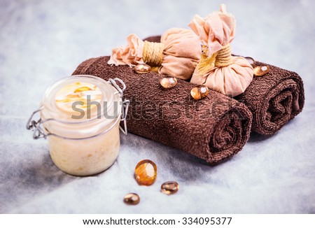 Spa treatment composition: container with body cream, towels, and decorative elements - stock photo