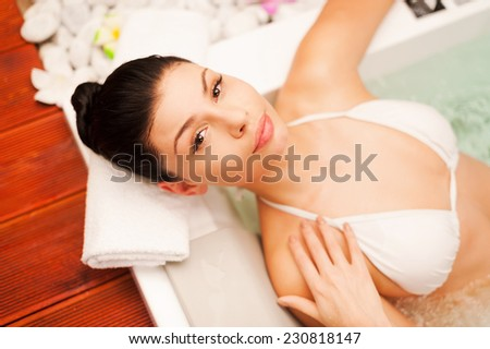 Spa treatment. Top view of beautiful young black hair woman relaxing in hot tub and touching her face - stock photo