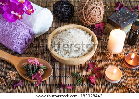 Spa with natural bath salt, candles, soap, towels and petals - stock photo