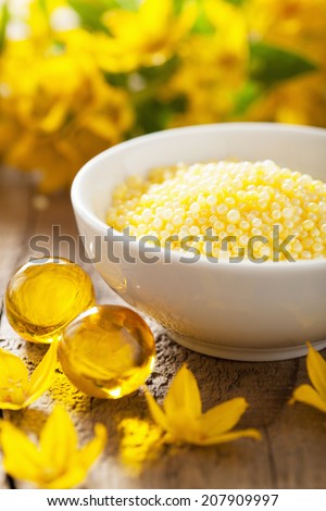 spa with yellow herbal bath pearls and flowers - stock photo