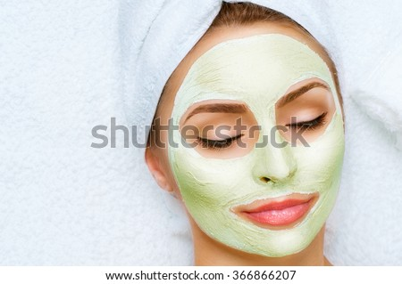 Spa Woman applying Facial clay Mask. Beauty Treatments. Close-up portrait of beautiful girl with a towel on her head applying facial mask - stock photo