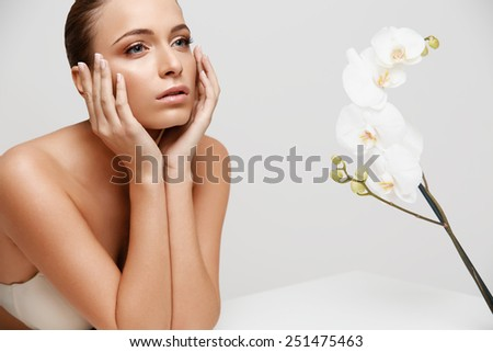 Spa Woman. Beautiful Girl Touching Her Face. Perfect Skin. Skincare. Wellness advertising - stock photo