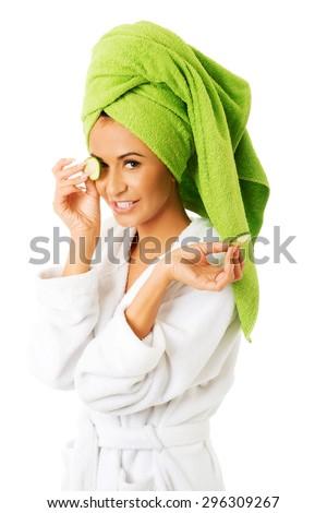 Spa woman in bathrobe applying cucumber on eyes. - stock photo
