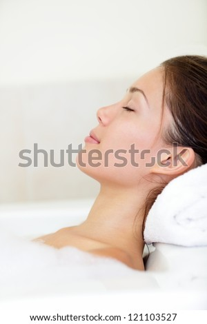 Spa woman relaxing in bath relaxed and serene with closed eyes. Pretty young mixed race Asian / Caucasian female model. - stock photo
