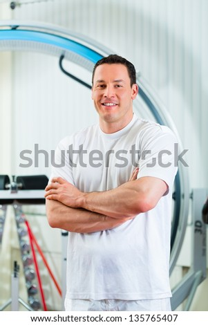 Space Curl - Portrait of a physical therapist in his practice in front an exercise machine - stock photo