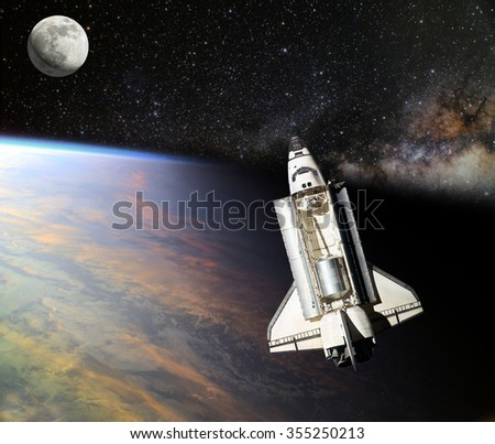 Space Shuttle orbiting the earth. Elements of this image furnished by NASA. - stock photo
