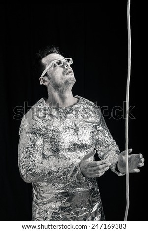 Spaceman with rope looking up. - stock photo