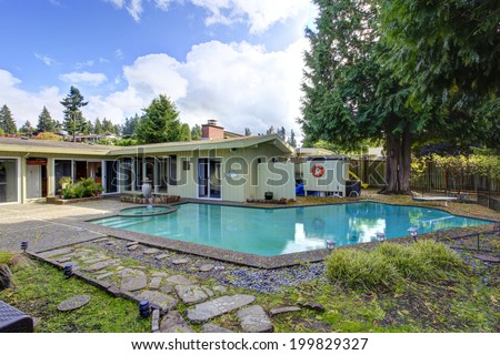 Spacious backyard view. One story house with swimming pool - stock photo