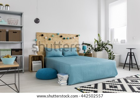 Spacious bedroom with large bed, blue bedding and simple, new furniture, white walls - stock photo