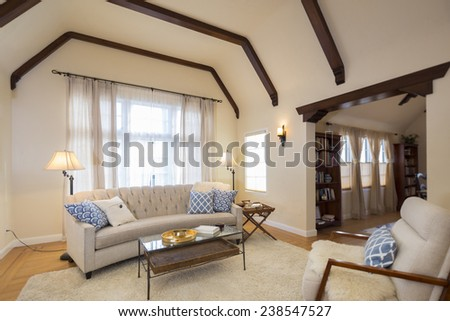 Spacious bright Craftsman home interior with beautiful inlaid hardwood floors, high ceilings with dramatic corbel beams, arched niches, white handwoven rug and blurred out library area. - stock photo