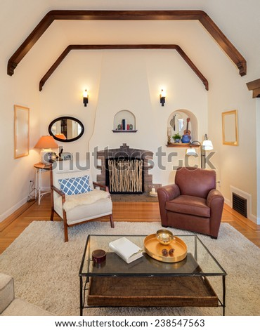 Spacious bright Craftsman home interior with beautiful inlaid hardwood floors, high ceilings with dramatic corbel beams, arched niches, white handwoven rug and a cozy fireplace - stock photo