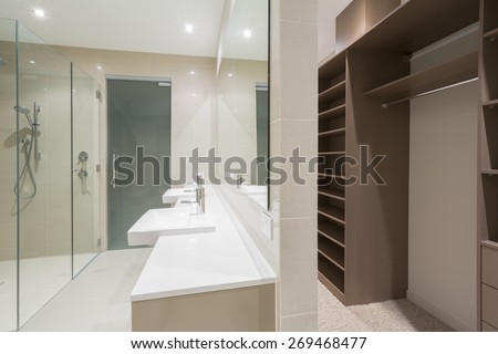 Spacious contemporary bathroom with shower and walk in robe - stock photo