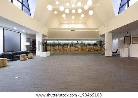 Spacious hotel lobby with reception desk - stock photo