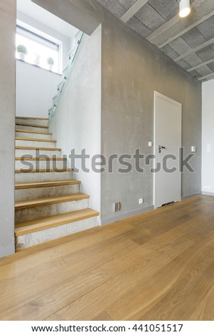 Spacious interior with a wooden flooring and stairs - stock photo