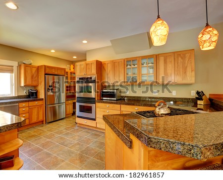 Spacious kitchen room with tile floor, wood cabinets and steel appliances - stock photo
