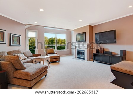 Spacious living room with fireplace and walkout deck. - stock photo